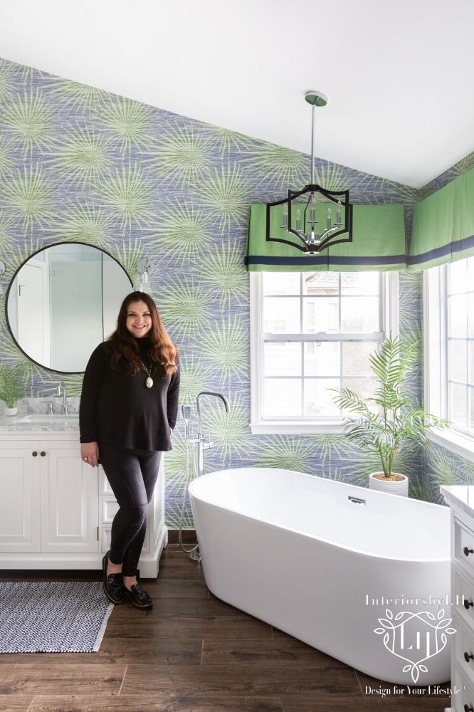 Designer Laura Hildebrandt standing in newly updated bathroom